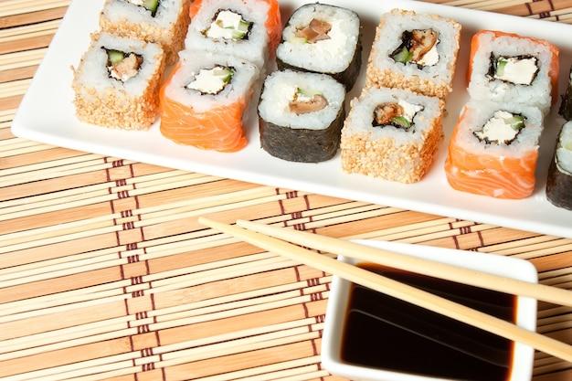 Sushi-assortiment op witte plaat, met sojasaus over bamboe achtergrond.