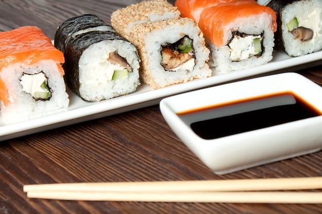 Sushi-assortiment op witte schotel op bruine houten tafel