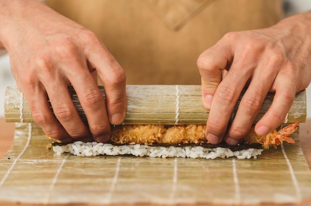 Sushi bereidingsproces close-up mannelijke handen rollen bamboe mat met sushi