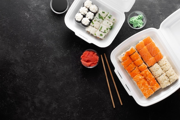 Sushi bezorgen. aziatisch eten in plastic bakjes op een zwarte achtergrond