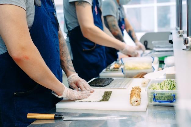 Sushi bezorgen. gemaskerde en gehandschoende koks bereiden sushi in de keuken van het restaurant.