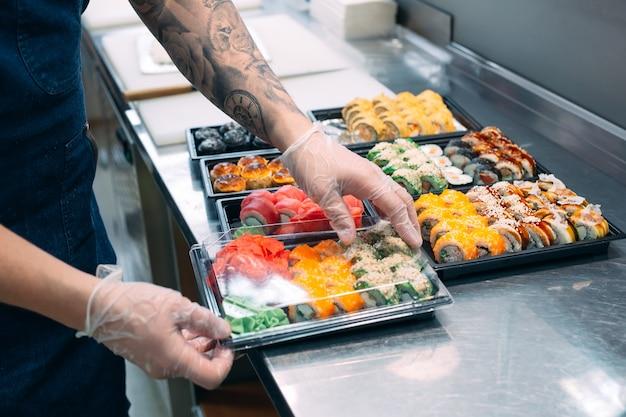 Sushi bezorgen. veel soorten sushi in een plastic doos zijn klaar voor levering.