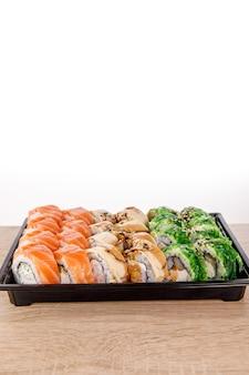 Sushi bezorgen. verschillende rollen in zwarte plastic verpakking bovenaanzicht componeren. japans en aziatisch eten. menu of leveringsconcept met ruimte voor tekst.