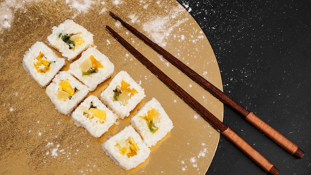 Sushi bezorgen. zoete broodjes gemaakt van rijst, ananas, kiwi en mango. rollen op een gouden en zwarte achtergrond. houten stokken voor sushi.