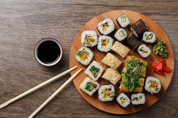 Sushi die bij ronde houten plaat worden geplaatst