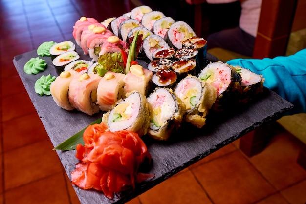 Sushi die op het zwarte close-up van de steenlei worden geplaatst.
