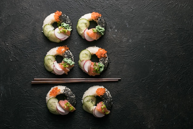 Sushi donuts met zalm, komkommer en radijs op donkere bovenaanzicht