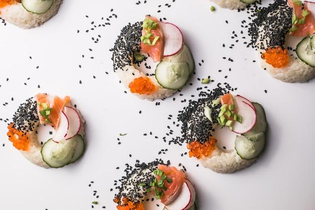 Sushi donuts met zalm, komkommer en radijs op witte bovenaanzicht