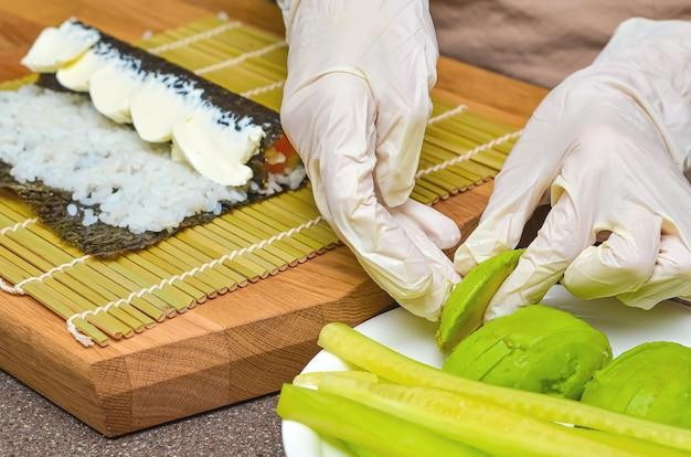 Sushi en broodjes voorbereidingsproces, bovenaanzicht, avocado voor japanse sushi.