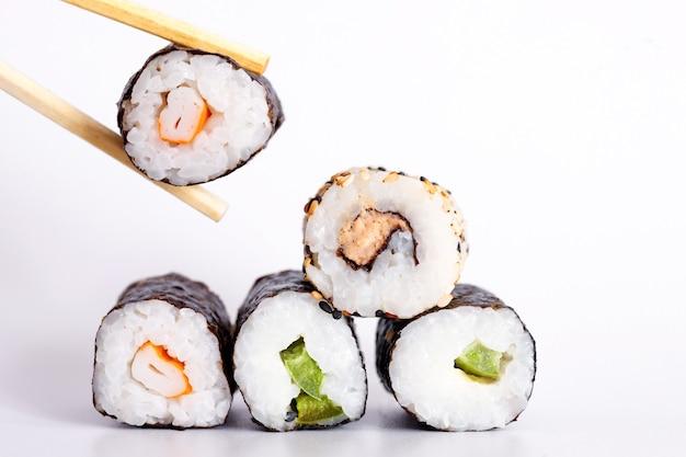 Sushi eten met stokjes. sushi roll japans eten in restaurant geïsoleerd op een witte achtergrond.