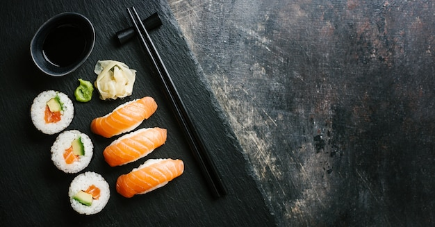 Sushi geserveerd op plaat op donkere tafel