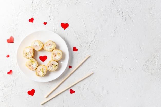 Sushi in de vorm van een hart op een witte plaat, valentijnsdag.