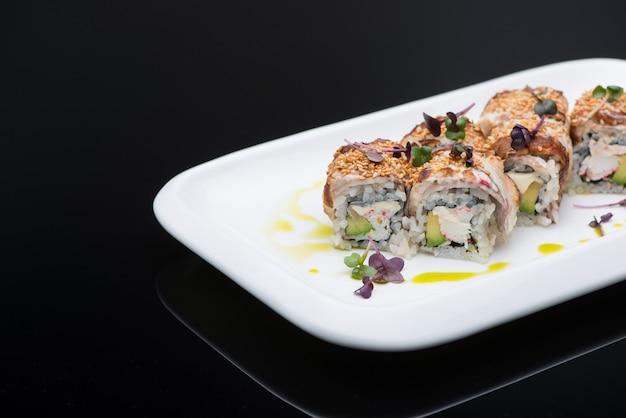 Sushi in een bord op een zwarte achtergrond met reflectie. visrolletje