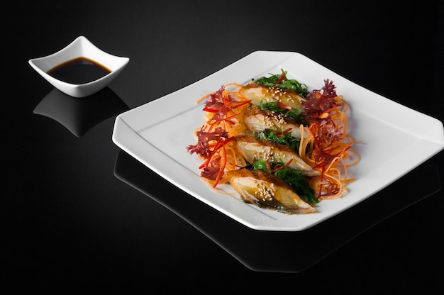 Sushi in een witte plaat met saus en soja op een zwarte achtergrond met reflectie