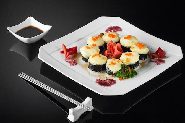 Sushi in een witte plaat met sauspot en eetstokjes op een zwarte achtergrond met reflectie
