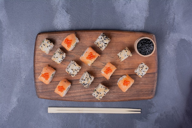 Sushi instellen. philadelphia en alaska broodjes op houten plaat met stokjes.