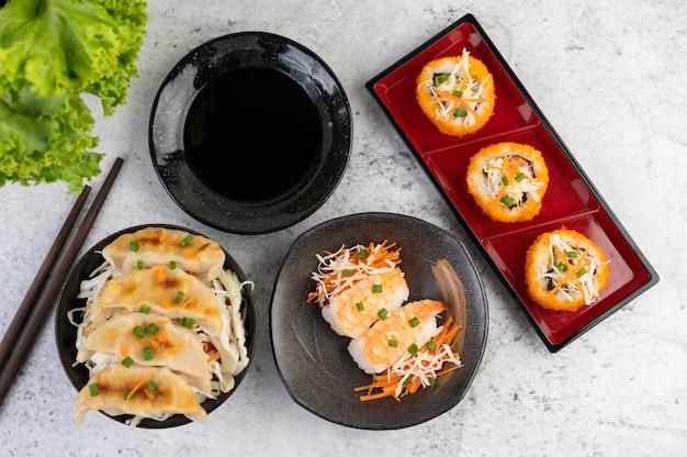 Sushi is in een bord met stokjes en dipsaus op een witte cementvloer.