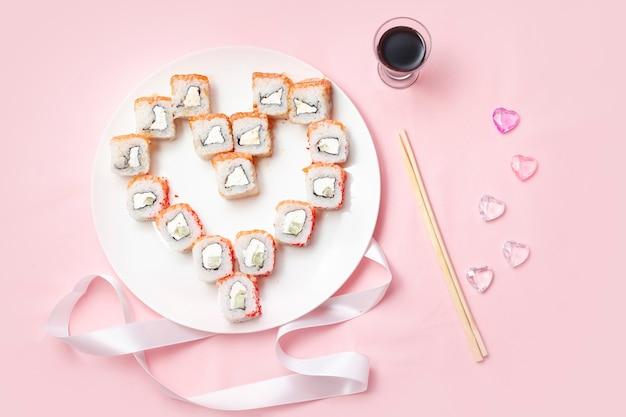Sushi is neergelegd in de vorm van een hart op een roze tafel met stokjes en sojasaus.
