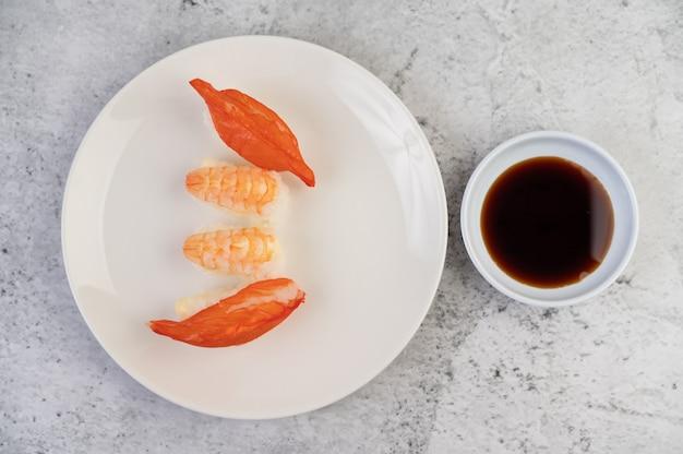 Sushi is op een bord met dipsaus op een witte cementvloer.