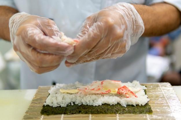 Sushi koken in het restaurant. handen close-up.