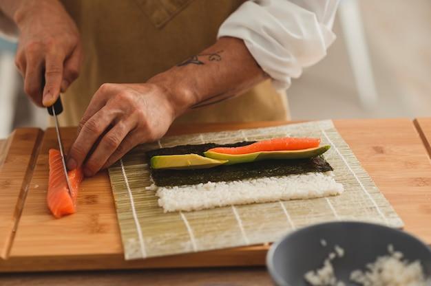 Sushi maken proces professionele mannelijke chef-kok in uniform snijden van zalmvis ingrediënten voorbereiden voor