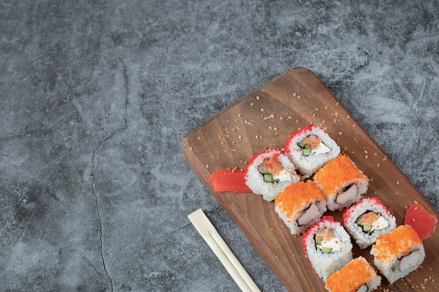 Sushi maki met rode kaviaar en roomkaas op een houten bord.