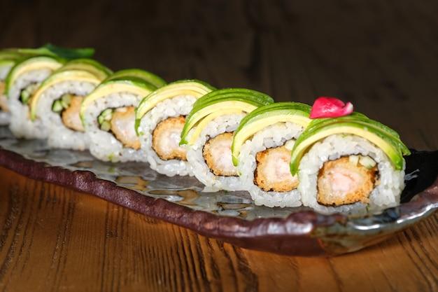 Sushi met gefrituurde gepaneerde garnalen komkommer avocado en teriyaki saus