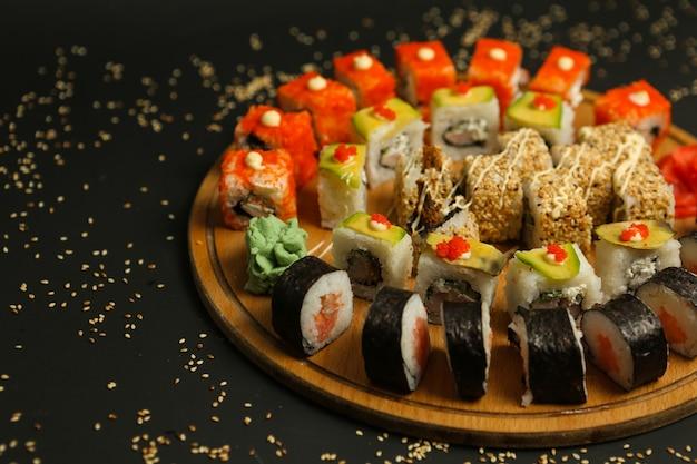 Sushi met het zijaanzicht dat van de tonijngroenten van de zalmgarnaal worden geplaatst