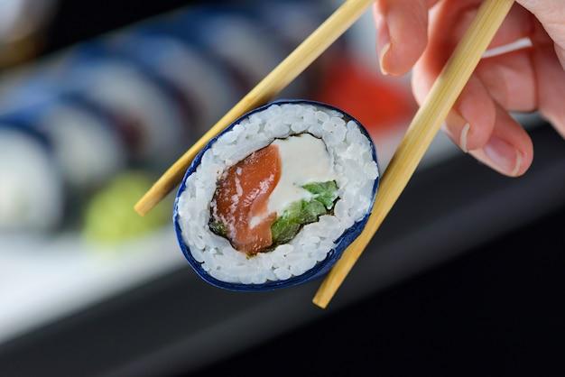 Sushi met in hand eetstokjes.