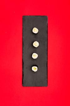 Sushi met komkommer in rij op zwart leiendienblad dat over rode achtergrond wordt geschikt