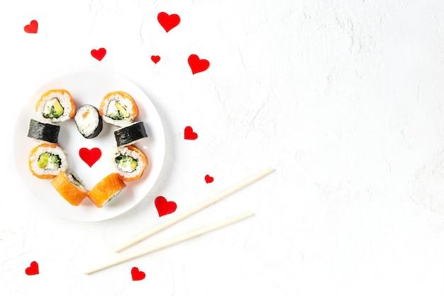 Sushi met rode harten op een witte plaat, valentijnsdag.