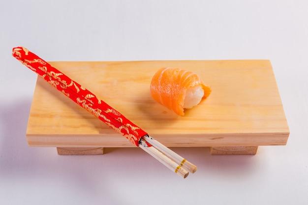 Sushi met roze zalm op een houten bord en eetstokjes.
