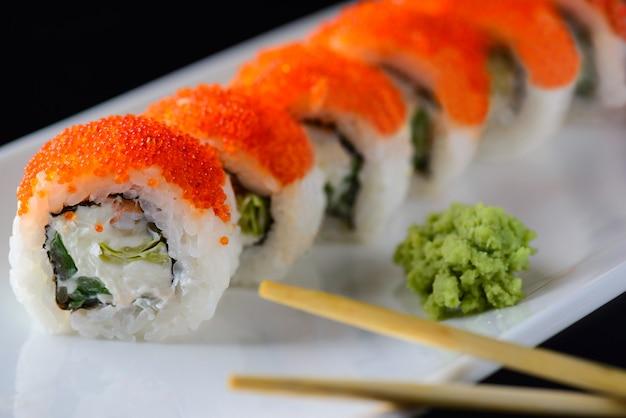 Sushi met vliegende vissenkaviaar en wasabi op een witte plaat.