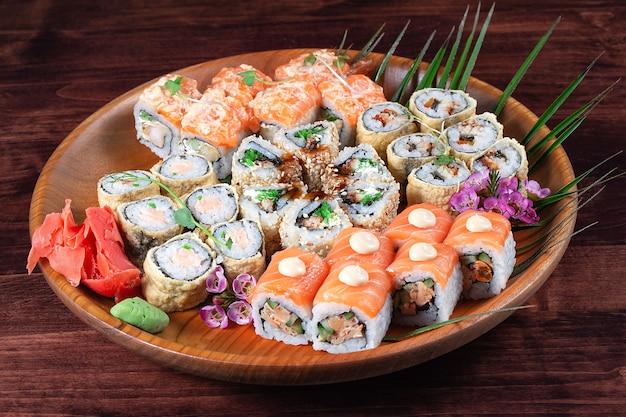 Sushi of broodjes met gember en kruiden op een houten bord met groene bladeren