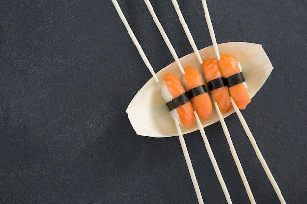Sushi op boot vormige plaat met stokjes