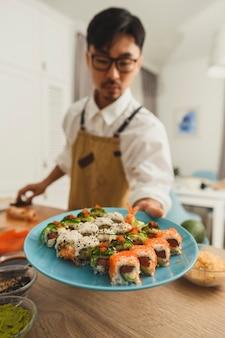 Sushi op een bord chef-kok geeft een bord aan het frame voedselbezorging online service japans
