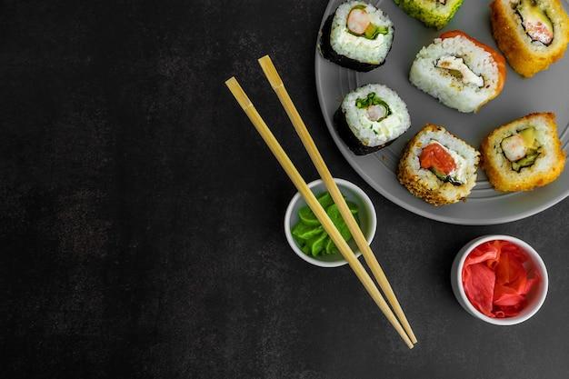 Sushi op een grijze plaat op een donkere achtergrond bovenaanzicht met gember en wasabi