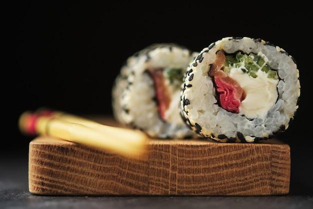 Sushi op een houten bord. rollen met vis op een donkere achtergrond.