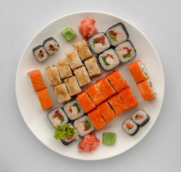 Sushi op een ronde plaat op een witte achtergrond. sushi roll close-up, bovenaanzicht