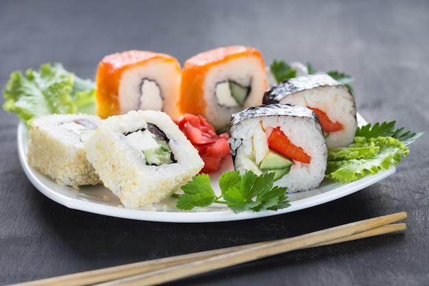 Sushi op een vierkant wit bord met peterselie greens met stokken op de voorgrond. grijs