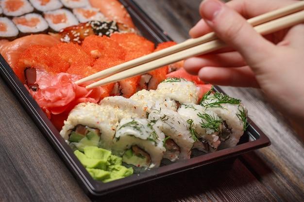 Sushi op een zwarte plaat en eetstokjes