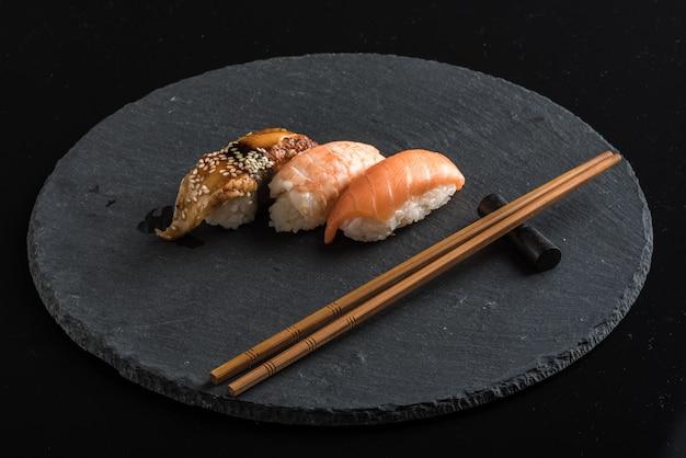 Sushi op een zwarte stenen plaat met stokjes