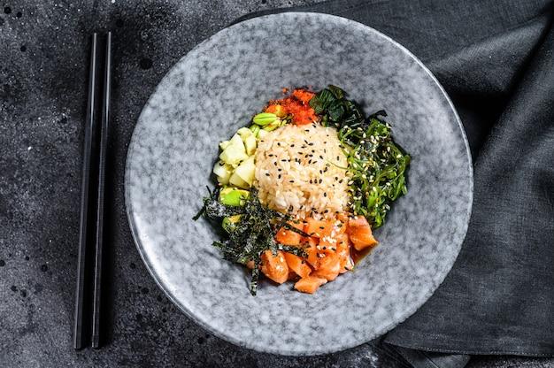 Sushi poke bowl met komkommer, zalm, avocado. aziatisch trendy eten. zwarte achtergrond. bovenaanzicht. kopieer ruimte.