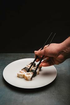 Sushi rijst roll zalm en kaas gepresenteerd op een witte plaat met de actie van een handgeplukte sushi