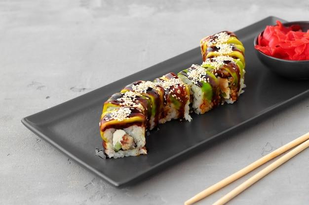 Sushi roll bedekt met avocado schillen op zwarte keramische plaat