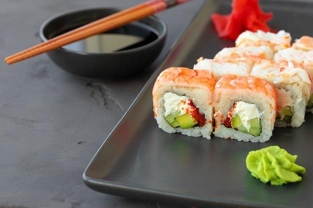 Sushi roll bedekt met garnalenvlees op zwarte keramische plaat close-up