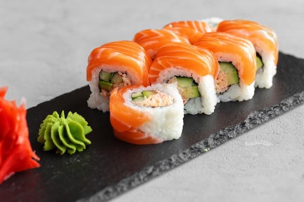 Sushi roll bedekt met verse zalm geserveerd op plaat close-up