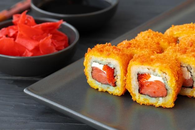 Sushi roll gebakken in tempura op zwarte plaat close-up
