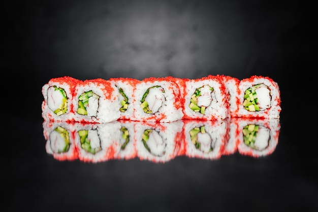 Sushi roll gemaakt van nori, pickled rice, philadelphia cheese, cucumber, salmon