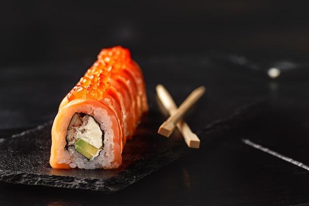 Sushi roll maki futo japans eten op een zwarte stenen plaat in de handen van een ober.